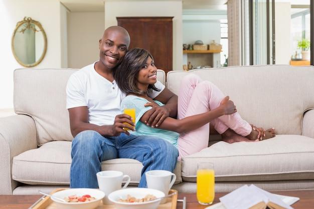 Glückliches paar, das auf der couch mit frühstück sich entspannt
