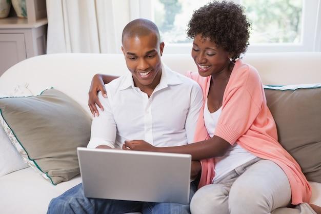 Glückliches paar, das auf der couch mit laptop sich entspannt