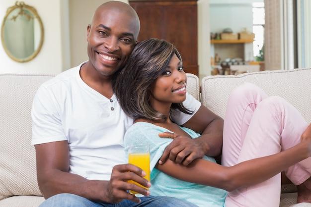 Glückliches paar, das auf der couch mit saft sich entspannt