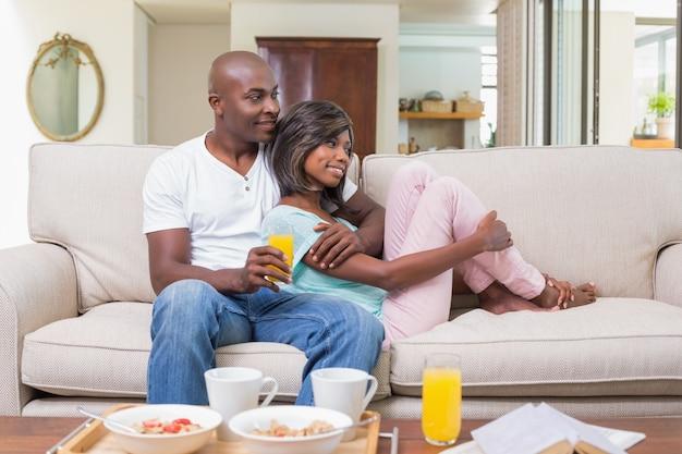 Glückliches paar, das auf der couch sich entspannt