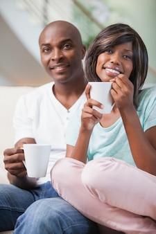 Glückliches paar, das auf der couch trinkt kaffee sitzt