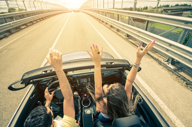 Glückliches paar, das auf der straße in den sonnenuntergang in einem sportwagen fährt
