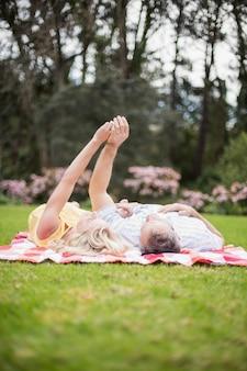 Glückliches paar, das auf einer decke auf dem gras umarmt