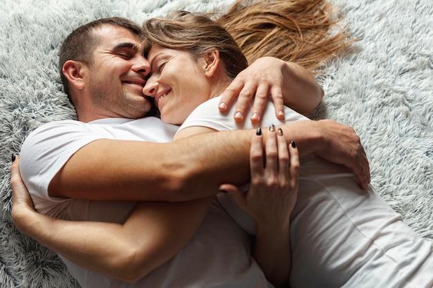 Glückliches paar, das auf einer decke umarmt