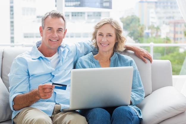 Glückliches paar, das auf ihrer couch unter verwendung des laptops sitzt, um online zu kaufen