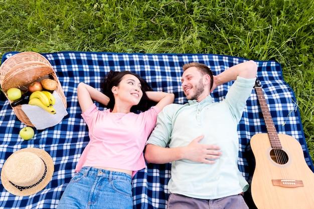 Glückliches paar, das auf picknickplaid stillsteht