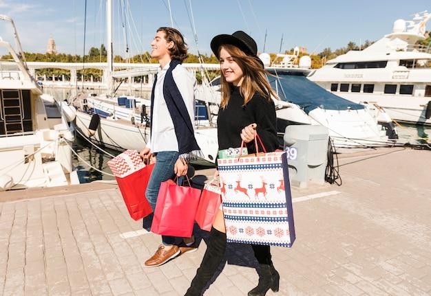 Glückliches paar, das auf pier mit einkaufstaschen geht