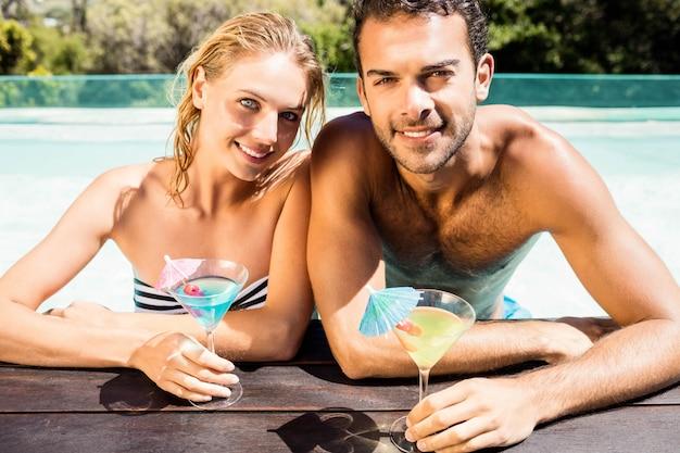 Glückliches paar, das auf poolrand sich lehnt und cocktails an einem sonnigen tag hält