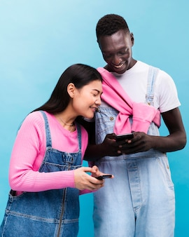 Glückliches paar, das auf smartphones schaut