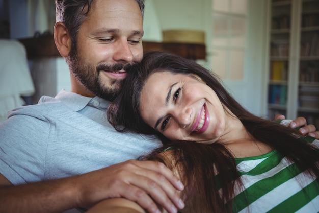 Glückliches paar, das auf sofa im wohnzimmer liegt
