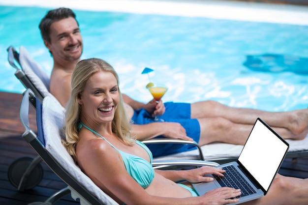 Glückliches paar, das auf sonnenliege nahe pool sitzt
