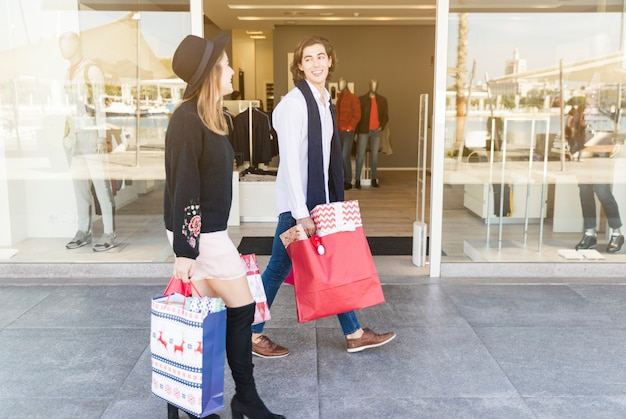 Glückliches paar, das auf straße mit einkaufstaschen geht