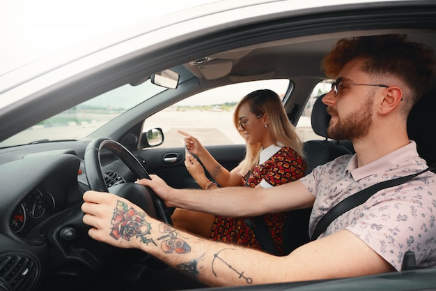Glückliches paar, das auto fährt und gps-navigator verwendet