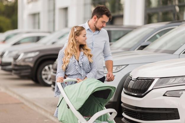 Glückliches paar, das autos betrachtet
