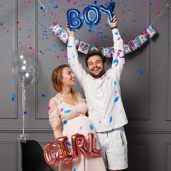 Glückliches paar, das ballons mit aufschrift junge oder mädchen während des geschlechts hält, enthüllt party, über konfetti und ballons.