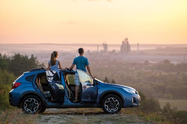 Glückliches paar, das bei sonnenuntergang in der nähe ihres autos steht. junger mann und frau genießen die gemeinsame zeit mit dem fahrzeug.