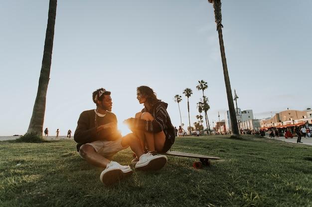 Glückliches paar, das bei sonnenuntergang sich entspannt