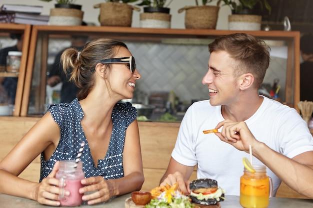 Glückliches paar, das beim ersten date lebhafte gespräche führt und freudige und sorglose ausdrücke hat