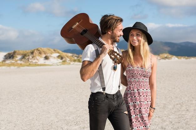 Glückliches paar, das beim gehen auf dem strand umarmt, der eine gitarre hält