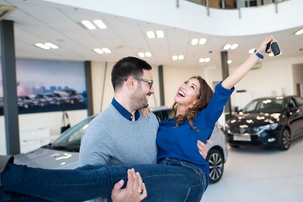 Glückliches paar, das brandneues auto beim örtlichen autohaus kauft