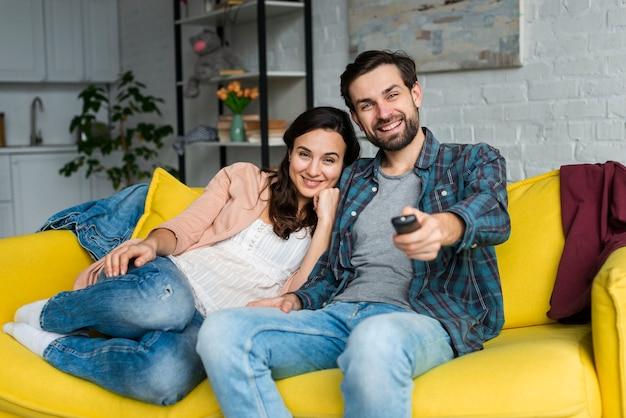 Glückliches paar, das den fernseher betrachtet