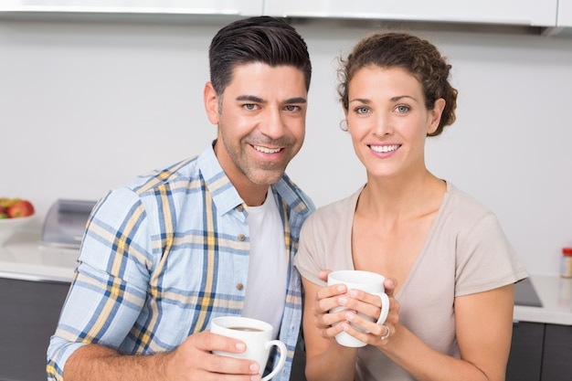 Glückliches paar, das den kaffee lächelt an der kamera trinkt