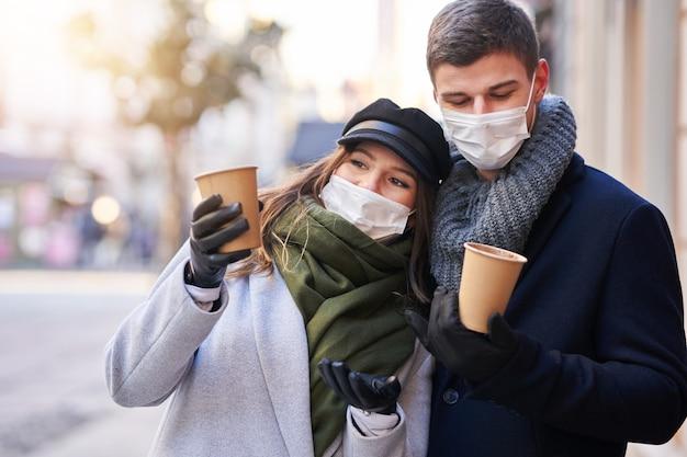 Glückliches paar, das den valentinstag in masken während der covid-19-pandemie in der stadt feiert