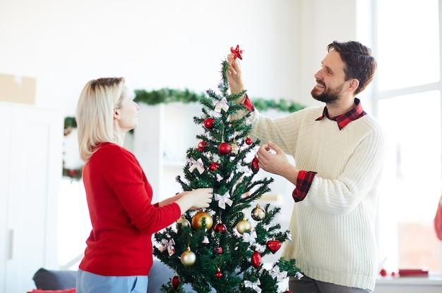 Glückliches paar, das den weihnachtsbaum schmückt