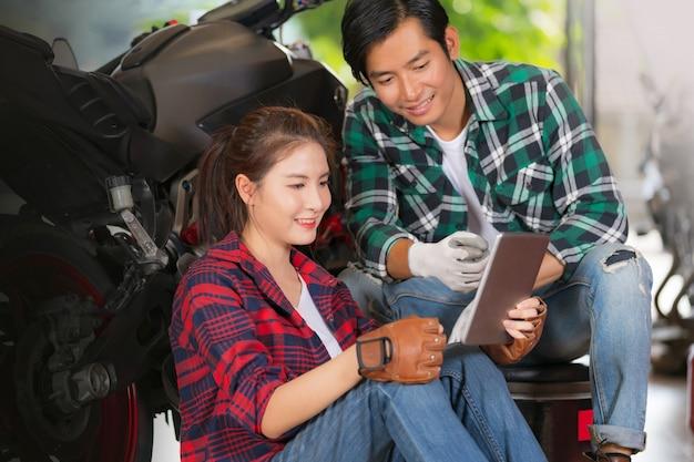 Glückliches paar, das digitale tablette an der reparatur und am kundenspezifischen motorradshop verwendet