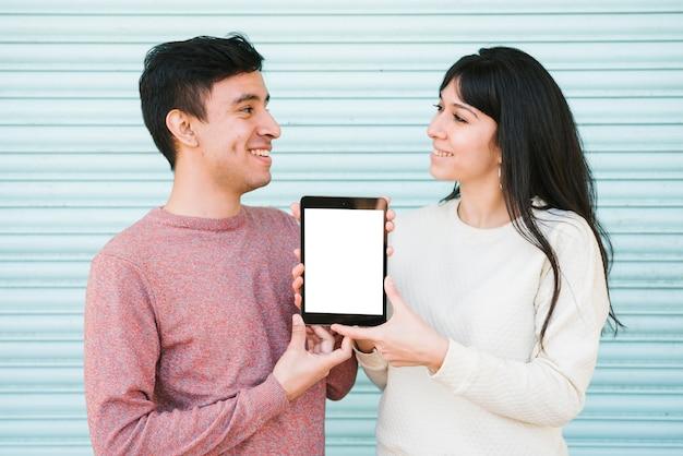 Glückliches paar, das digitale tablette zeigt
