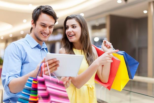 Glückliches paar, das digitales tablett während des einkaufs verwendet