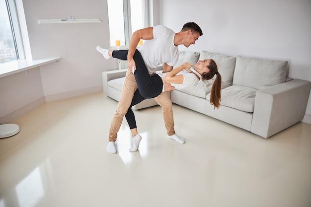 Glückliches paar, das dip-tanzbewegungen macht, während es zu hause tanzt