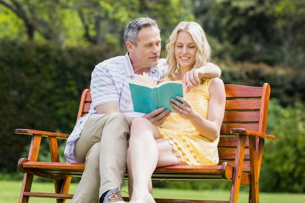 Glückliches paar, das draußen ein buch auf der bank liest