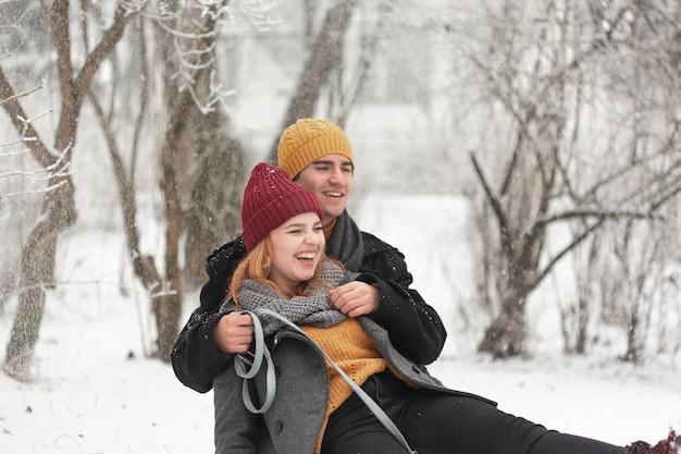 Glückliches paar, das draußen im schnee spielt