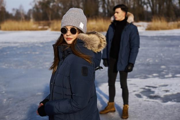 Glückliches paar, das draußen im winter umarmt und lacht.