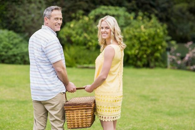 Glückliches paar, das draußen picknickkorb hält