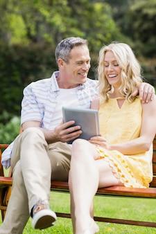 Glückliches paar, das draußen tablette auf einer bank verwendet