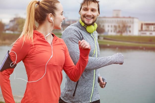 Glückliches paar, das draußen trainiert. einen partner zu haben, erleichtert den lauf erheblich