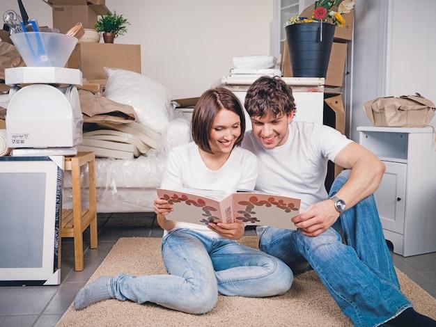 Glückliches paar, das durch das fotoalbum schaut, das zusammen auf dem boden sitzt