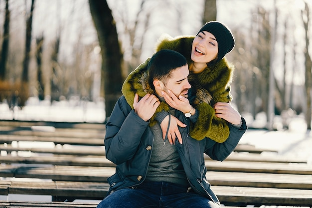 Glückliches paar, das durch den park an einem sonnigen wintertag geht