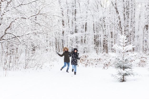 Glückliches paar, das durch einen verschneiten wald im winter geht