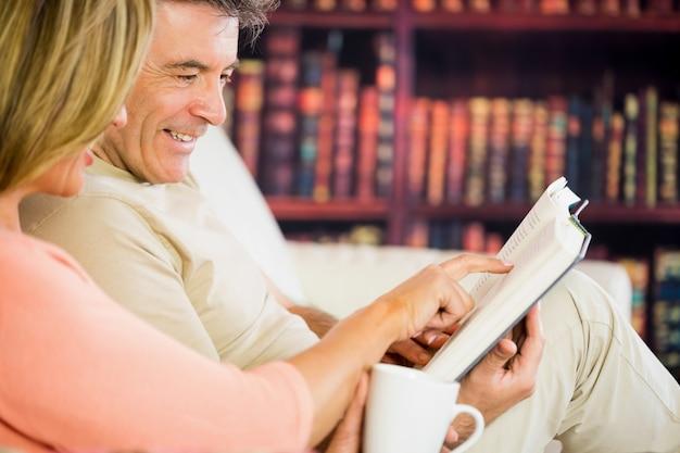 Glückliches paar, das ein buch in einem lesesaal liest und kaffee trinkt