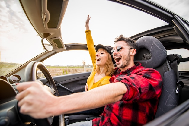 Glückliches paar, das ein cabrioauto bei sonnenuntergang auf der straße fährt