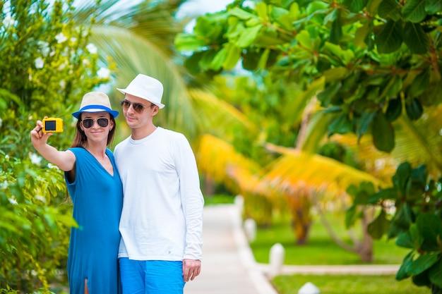 Glückliches paar, das ein foto am weißen strand im flitterwochenurlaub macht