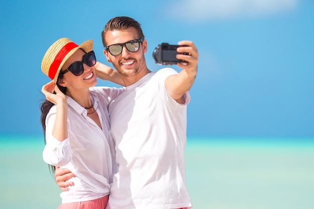 Glückliches paar, das ein foto auf weißem strand am flitterwochenfeiertag macht