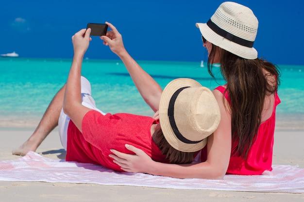 Glückliches paar, das ein foto selbst auf tropischem strand macht