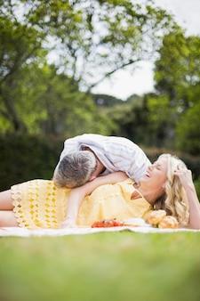 Glückliches paar, das ein picknick draußen hat