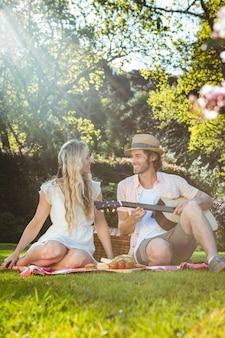 Glückliches paar, das ein picknick hat und gitarre im garten spielt