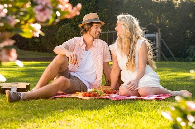 Glückliches paar, das ein picknick im garten hat