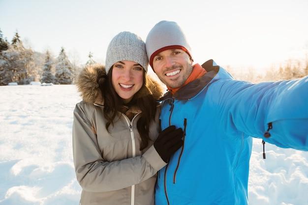 Glückliches paar, das ein selfie auf verschneiter landschaft nimmt